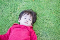 Closeup cute asian kid lie on grass floor in park textured background with copy space. Closeup cute kid lie on grass floor in park textured background with copy Stock Image