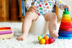 Closeup of cute little 12 months old toddler baby girl child sitting on potty. Kid playing with educational wooden toy. Toilet training concept. Baby learning Stock Photo