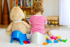 Closeup of cute little 12 months old toddler baby girl child sitting on potty. Kid playing with big plush soft toy stock image