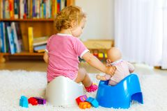 Closeup of cute little 12 months old toddler baby girl child sitting on potty. Kid playing with doll toy. Toilet royalty free stock image