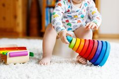 Closeup of cute little 12 months old toddler baby girl child sitting on potty. Kid playing with educational wooden toy. Toilet training concept. Baby learning stock image