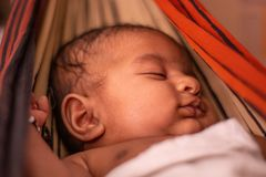 Closeup of cute little new born baby sleeping in cradle made of saree in India.  royalty free stock photo