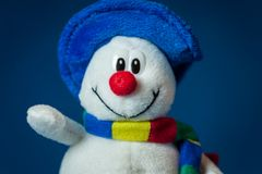 A cute little soft snowman with a blue hat and a colorful scarf Stock Image