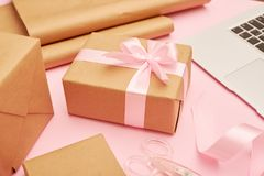 Cute present box with laptop placing on pink flatlay Stock Photos