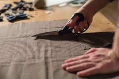 Closeup cutting brown plaid wool fabric. the line pattern. Young man working as a tailor and using a sewing machine in. Cutting brown plaid wool fabric. the line royalty free stock photography