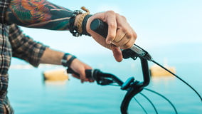 Closeup Of A Cyclist Hand On Bike Handlebars, Holiday Activity Transportation Concept. Unrecognizable male cyclist holding hands on handlebars, close-up Stock Photos