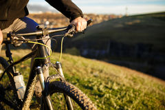 Closeup of cyclist hand on handlebar. Unrecognizable sportsman riding his bicycle on sunny spring day. Royalty Free Stock Photo