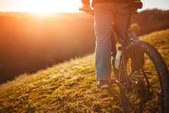 Closeup of cyclist man legs and hands riding mountain bike on outdoor trail in nature Stock Photography