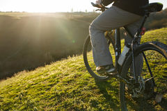 Closeup of cyclist man legs and hands riding mountain bike on outdoor trail in nature Royalty Free Stock Photography
