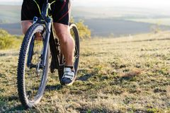 Closeup of cyclist man legs and hands riding mountain bike on outdoor trail in nature Royalty Free Stock Photos