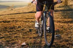 Closeup of cyclist man legs and hands riding mountain bike on outdoor trail in nature Stock Photos