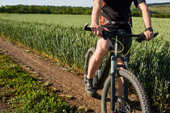 Closeup of cyclist man legs with mountain bike on outdoor trail in the summer field. Young cyclist dressed in the sportwear and sporty shoes. Sporty Royalty Free Stock Image