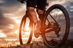 Cyclist man legs riding mountain bike on outdoor trail. Closeup of cyclist man legs riding mountain bike on outdoor trail in autumn forest Stock Photography