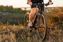 Closeup of cyclist man legs riding mountain bike on outdoor trail. Closeup of cyclist man legs riding mountain bike on meadow against sunset Stock Image
