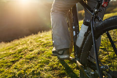 Closeup of cyclist man legs riding mountain bike on outdoor trail on the green field. Low angle. Detail of the bicycle. Wheel and bottle. Legs and shoes Stock Image