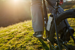 Closeup of cyclist man legs riding mountain bike on outdoor trail on the green field. Low angle. Detail of the bicycle. Wheel and bottle. Legs and shoes Royalty Free Stock Photography