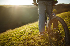 Closeup of cyclist man legs riding mountain bike on outdoor trail on the green field. Low angle. Detail of the bicycle. Wheel and bottle. Legs and shoes Royalty Free Stock Photo