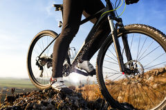 Closeup of cyclist man legs riding mountain bike on outdoor trail on hill Stock Image