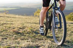 Closeup of cyclist man legs riding mountain bike on outdoor trail. Closeup of cyclist man legs riding mountain bike on meadow against sunset Stock Images