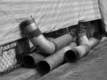 Old metal pipes. Closeup of damaged metal pipes on concrete floor, monochrome stock photography