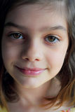 Closeup of dark eyed little girl. A dramatic portrait of a smiling dark haired, dark eyed little girl. Shallow depth of field Stock Image