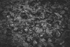 Closeup of dark rock textured background. Gray rough stone texture and background for design.