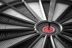 Closeup of a dart in the red center of black and grey dartboard Royalty Free Stock Images