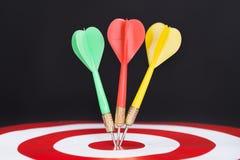Closeup of darts on target Stock Photos