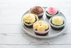 Frosted cupcakes on white plate on wooden table stock photos