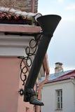 Closeup of a decorative boot-shaped drainpipe Stock Photos