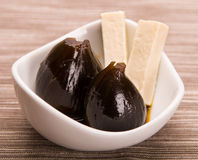 Closeup delicious caramelized figs dessert lying in a small white bowl with strips of fresh cheese Royalty Free Stock Photography