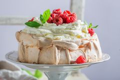 Delicious and crispy Pavlova cake with raspberries and meringue. Closeup of delicious and crispy Pavlova cake with raspberries and meringue Stock Photography