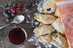 Closeup of a delicious pastry stuffed with berries, on wooden bo. Baking with jam from berries on a wooden board in rustic style decorated with frozen berries Stock Images