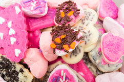 Closeup of delicious pile with cookies mostly pink. Colored frosting and some chocolate sprinkles Stock Images