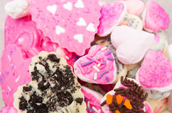 Closeup of delicious pile with cookies mostly pink. Colored frosting and some chocolate sprinkles Stock Photos