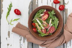 Closeup of delicious salad of arugula with cherry tomatoes and chicken breast in a clay bowl on a wooden table, top view. Sports n stock images