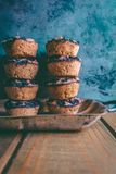Closeup of delicious tasty blueberry muffins stacked on top of each other with a sky blue background stock photography