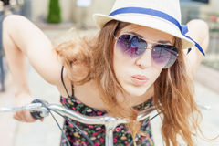 Closeup delight and enjoyment woman travel to Paris by bicycle. Closeup happy fashion woman with sunglasses, travel to Paris by city bicycle, she looks amazing Royalty Free Stock Image