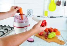 closeup Den oigenkännliga mannen trycker på moroten inom juiceren för att göra smaklig fruktsaft för frukost från nya grönsaker,  Arkivfoto