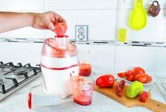 closeup Den oigenkännliga mannen trycker på tomater inom juiceren för att göra smaklig fruktsaft för frukost från nya grönsaker,  Royaltyfri Bild