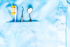 Closeup of dental tool, toothbrush and a mirror in white medical uniform pocket. Oral dental health concept stock photo