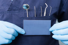 Closeup of dental tools and blue card in dentist hands Royalty Free Stock Photography