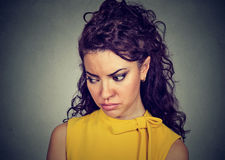 Closeup depressed sad woman looking down. Isolated on gray background Stock Photo