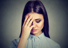 Closeup depressed sad woman looking down leaning head on hand. Isolated on gray background Stock Photo