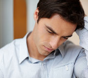 Closeup of a depressed young guy looking down Stock Image