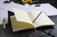 Closeup of designer`s notebook on table.Tools of designer during work.Concept of creating clothes collection royalty free stock image