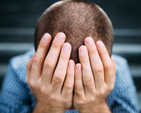 Closeup of despaired young man covering his face with hands. Closeup portrait of despaired young man covering his face with hands. Selective focus on hands stock images
