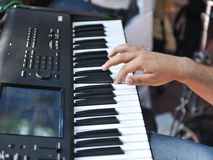 Closeup detail of a hand playing on piano keyboard Royalty Free Stock Photography