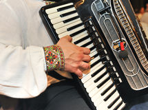 Closeup detail of hands playing a black accordion Royalty Free Stock Image