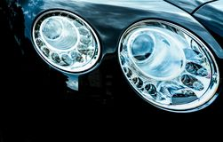 Closeup detail of LED headlight luxury car. Beautiful modern elegance headlamp car. Black automobile. Automotive industry. Technology. Auto parts business royalty free stock images